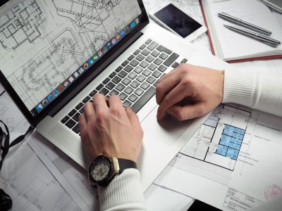 man hands laptop blueprints